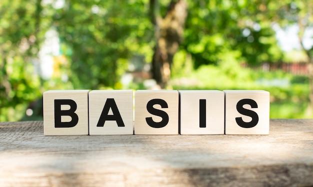 Пять деревянных блоков лежат на деревянном столе на фоне летнего сада и образуют слово basis.