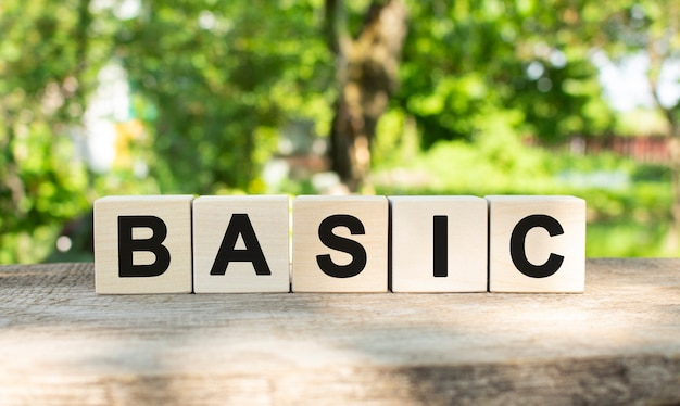 Five wooden blocks lie on a wooden table against the backdrop of a summer garden and create the word basic.