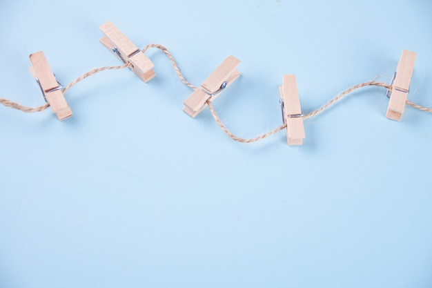 Five wooden clothespins on a rope on blue background