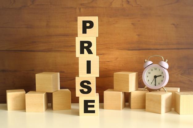 갈색 배경에 수직으로 쌓인 5개의 나무 큐브가 prise라는 단어를 구성합니다.