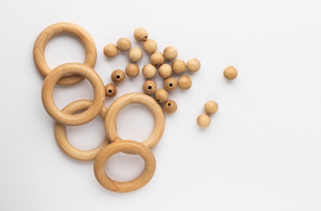 Пять деревянных колец и бус на белом фоне. прорезыватель для зубов из натурального дерева. экологичная детская игрушка.