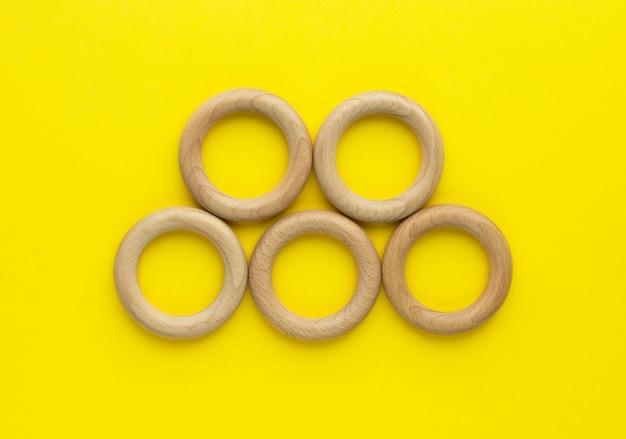 Пять деревянных колец на желтом фоне. прорезыватель для зубов из натурального дерева. экологичная детская игрушка. вид сверху, плоская планировка с копией пространства.