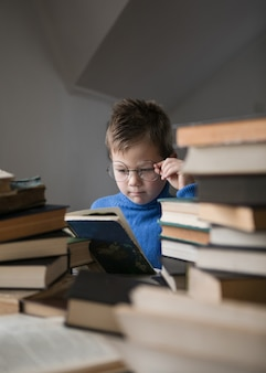 Five year old boy in glasses reading a book with a stack of books next to him.v