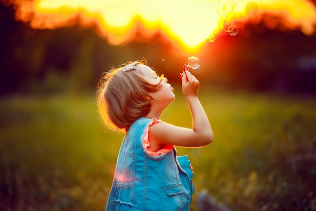 Five years old caucasian child girl blowing soap bubbles outdoor at sunset .