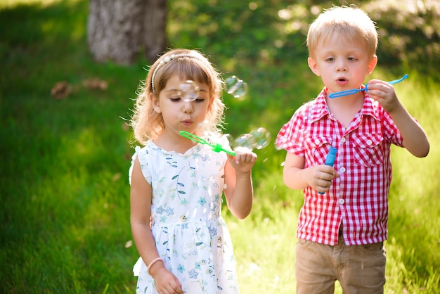 Five years old caucasian child girl and boy blowing soap bubbles outdoor at sunset - happy carefree childhood