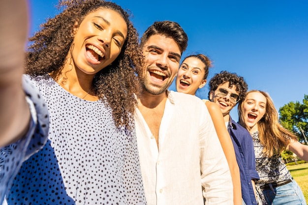 Five young multiracial friends in line posing for photo portrait smiling with open mouth
