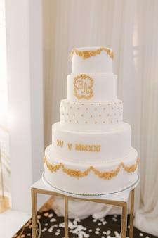 新郎と新婦のための金色の美しい甘いもので飾られた5階建ての白いウエディングケーキ