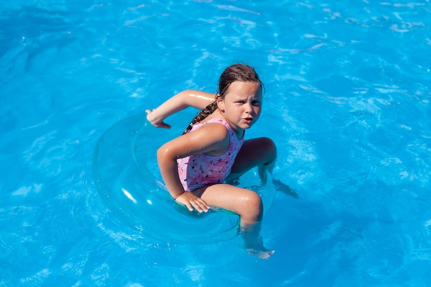 A fiveyearold girl in a pink swimsuit is angry that she cant keep her balance sitting on an inflatab...
