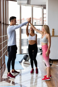 Мужчины и женщины, высоко-fiving в тренажерном зале