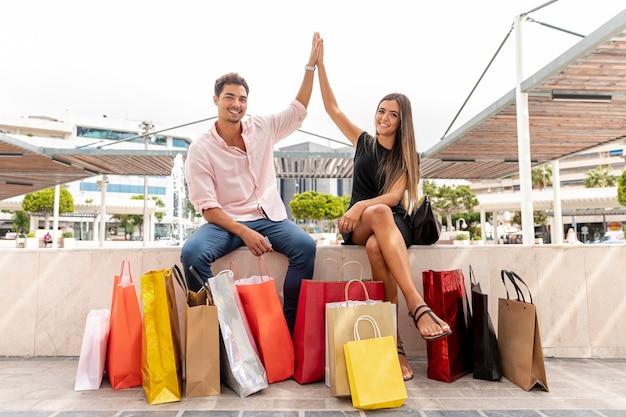 Счастливая пара сидит и высокий fiving