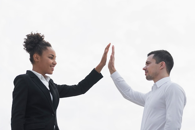 ビジネスの男性と女性の高いfiving