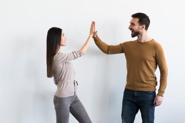 Положительный взрослый мужчина и молодая женщина высокого fiving