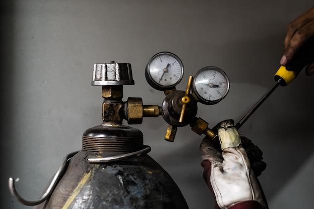プロパンガスタンクの固定。溶接用の液体ガスの圧縮シリンダーを修理する男性の手
