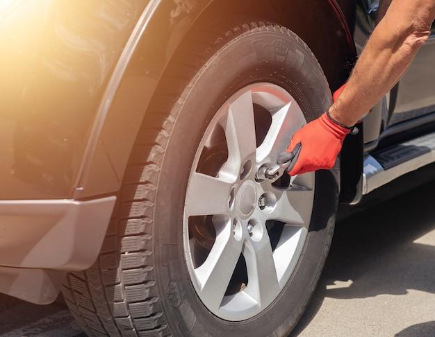 Крепление и проверка колесной шины автомобиля с помощью ручного металлического инструмента крупным планом