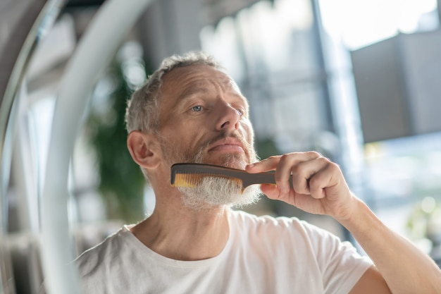Fixing beard style. a man styling his beard with a comb