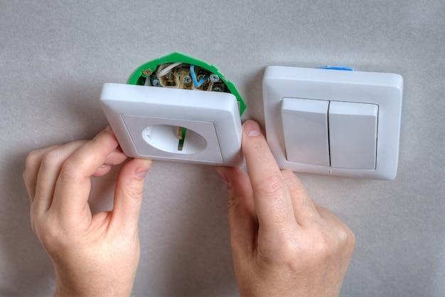 Ремонт электророзетки и выключателя света, руки слесаря электрика.