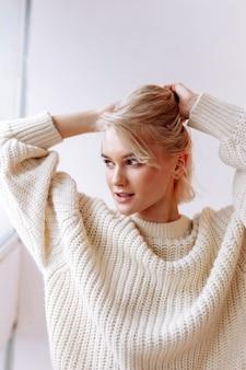 머리카락 고정. 아침에 그녀의 머리를 고정 좋은 베이지 색 스웨터를 입고 매력적인 젊은 여자