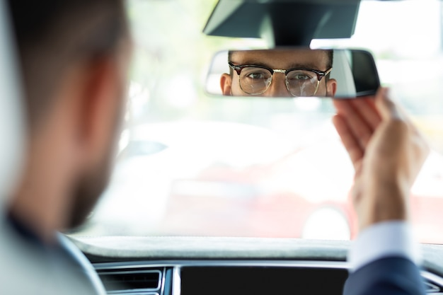 固定ミラー。彼の車を運転する前にバックミラーを固定する眼鏡をかけている若いビジネスマン