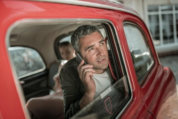 회의를 수정합니다. 그의 아내 앞 차 창 근처에 앉아 전화에 얘기 웃는 남자.