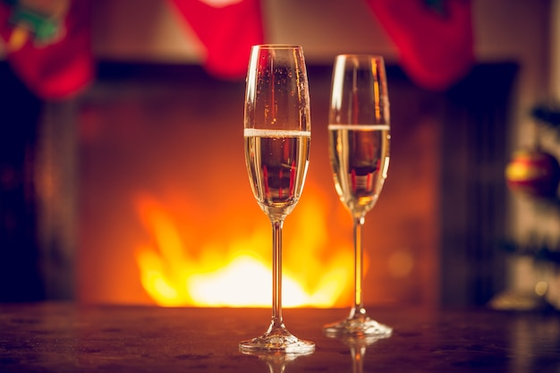 Fizzy champagne in two glasses on christmas table in front of fireplace
