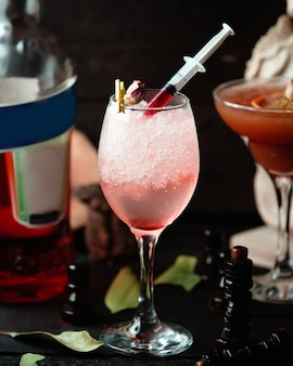 Fizzy drink in glass with red sauce garnished with dried rose petal