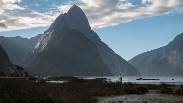 맨 아래에 우세한 봉우리와 사람이 있는 피요르드 풍경 밀포드 사운드 피오르드랜드 뉴질랜드