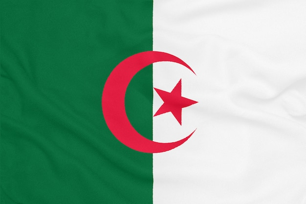 Flag of algeria on textured fabric. patriotic symbol