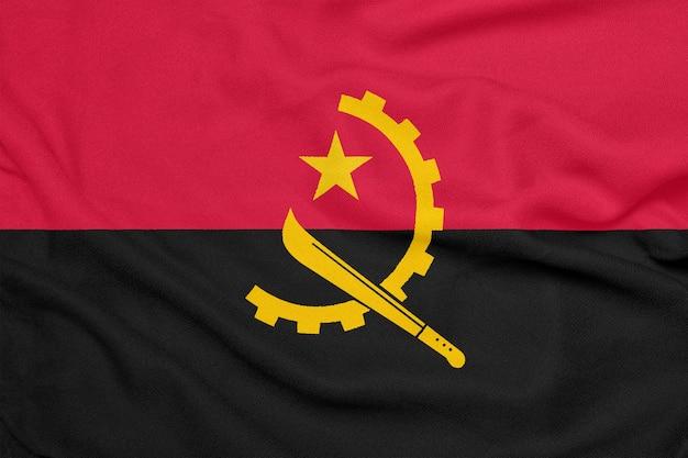 Flag of angola on textured fabric. patriotic symbol