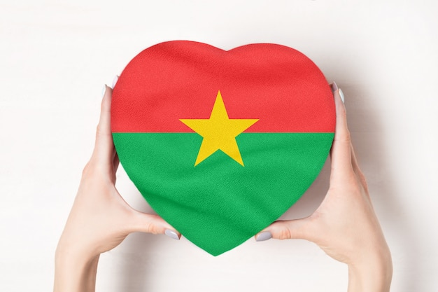 Flag of burkina faso on a heart shaped box in a female hands.
