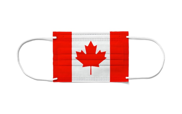 Flag of canada on a disposable surgical mask. white background isolated