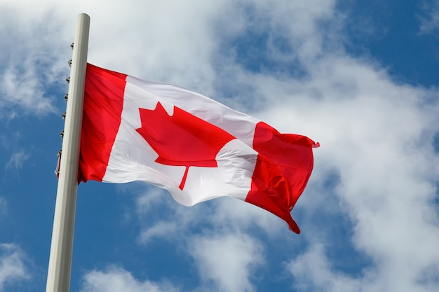 Flag of canada on a flagpole flutters in the wind against a bright blue sky with clouds