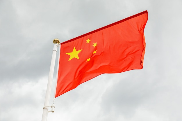 Flag of china against white sky with clouds