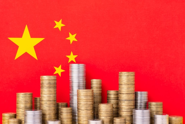 Flag of china with stacks of gold and silver coins Premium Photo