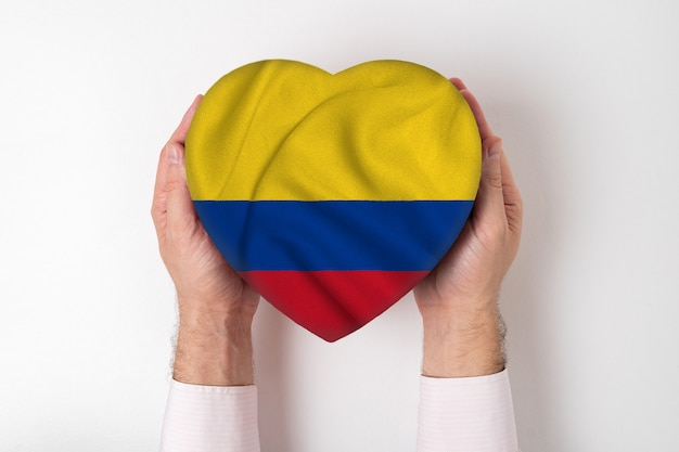 Flag of colombia on a heart shaped box in a male hands.