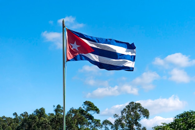 The flag of cuba waving in the wind against a clear blue sky.