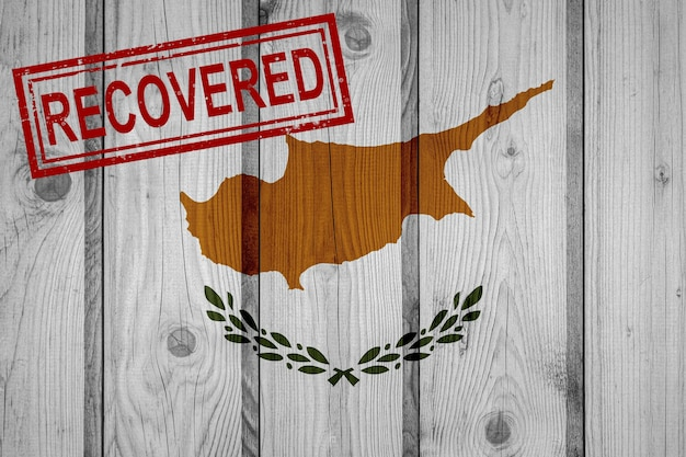Flag of cyprus that survived or recovered from the infections of corona virus epidemic or coronavirus. grunge flag with stamp recovered