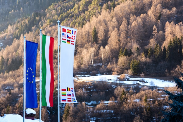 The flag of european union, italy and other countries are developing against the backdrop of dolomites in the spring.