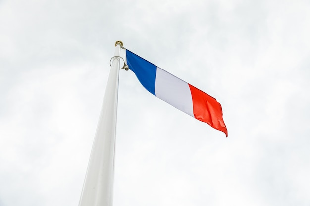 Flag of france in the sky on a flagstuff in front of the sky