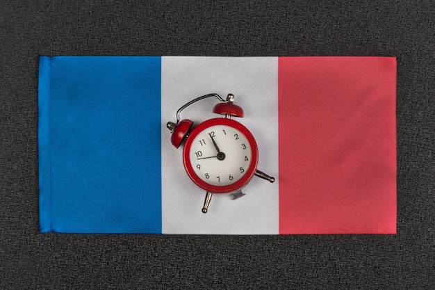 Flag of france and vintage alarm clock, close up. time to learn french