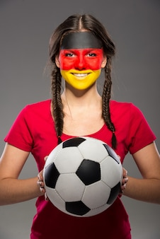 Flag of germany painted on a face of a young woman.