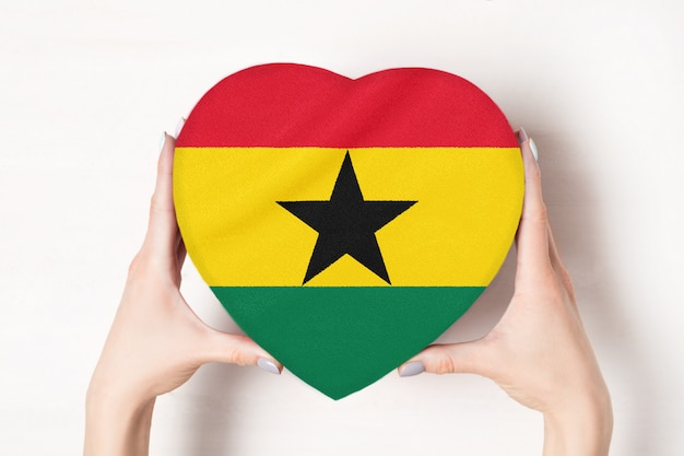 Flag of ghana on a heart shaped box in a female hands