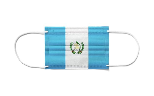 Flag of guatemala on a disposable surgical mask. white surface isolated