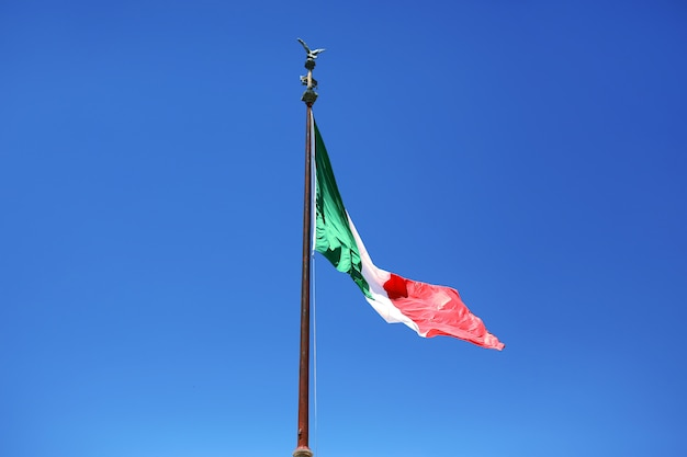 Flag of italy on a blue sky background. symbol of italy