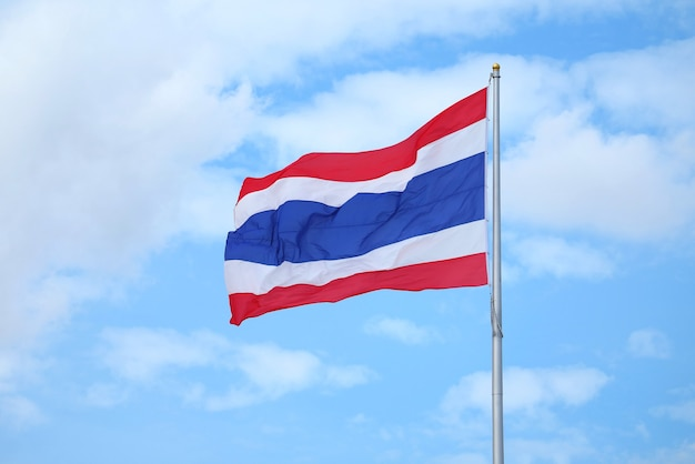 The flag of the kingdom of thailand called thong trai rong, meaning tricolour flag waving on blue sky