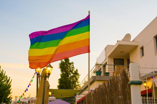 Флаг лгбт на фоне заходящего солнца в баре под открытым небом