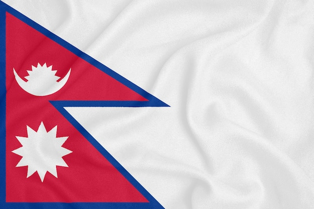 Flag of nepal on textured fabric. patriotic symbol