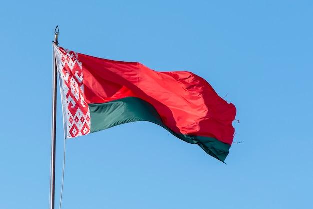 Флаг беларуси развевается против голубого неба