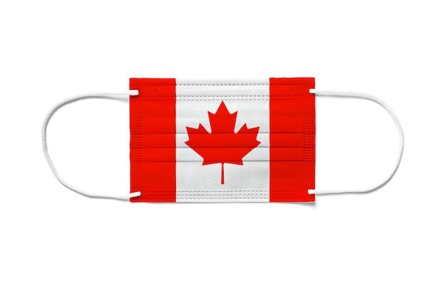 使い捨てサージカルマスクにカナダの旗。分離された白い背景