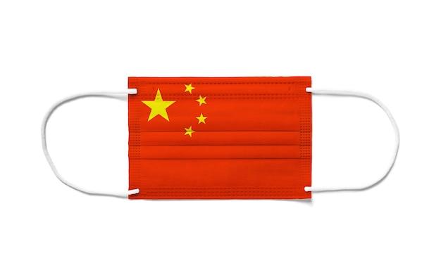 使い捨てサージカルマスクに中国の旗。分離された白い背景