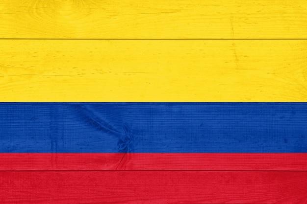 汚れた木の板の背景に描かれたコロンビアの旗